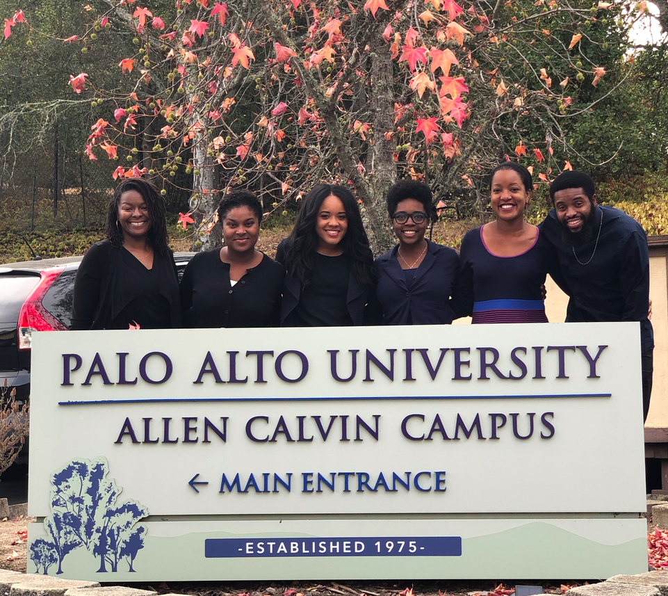 "outdoor photo of six people, all wearing black tops, visible from the waist up behind a large sign that reads ""Palo Alto University Allen Calvin Campus [arrow] main entrance, established 1975"""