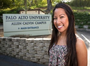 A student standing in front of Allen Calvin Campus main entrance at Palo Alto University in Palo Alto, CA