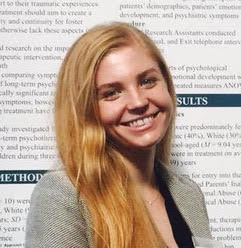 photo of a person with long light-red hair, standing in front of a research poster