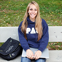Palo Alto University undergraduate psychology major on campus holding laptop