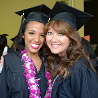 Two graduates from counseling program at Palo Alto University in Palo Alto, CA posing for a photo at graduation
