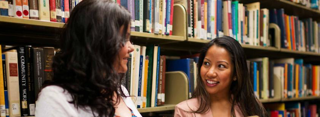 Two students talking in the library book stacks